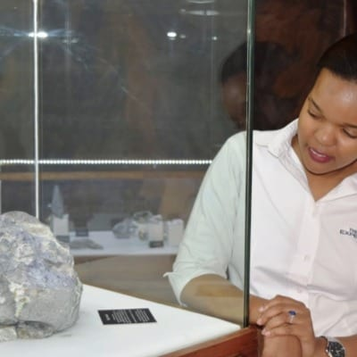A staff of the tanzanite experience showcasing a Tanzanite stone at the museum
